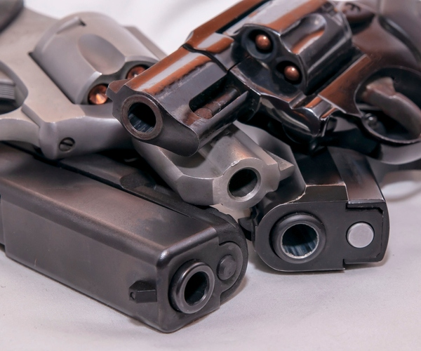 Four handguns, two pistols and two revolvers, a 9mm, 40 caliber, 357 magnum and a 38 special on a white background