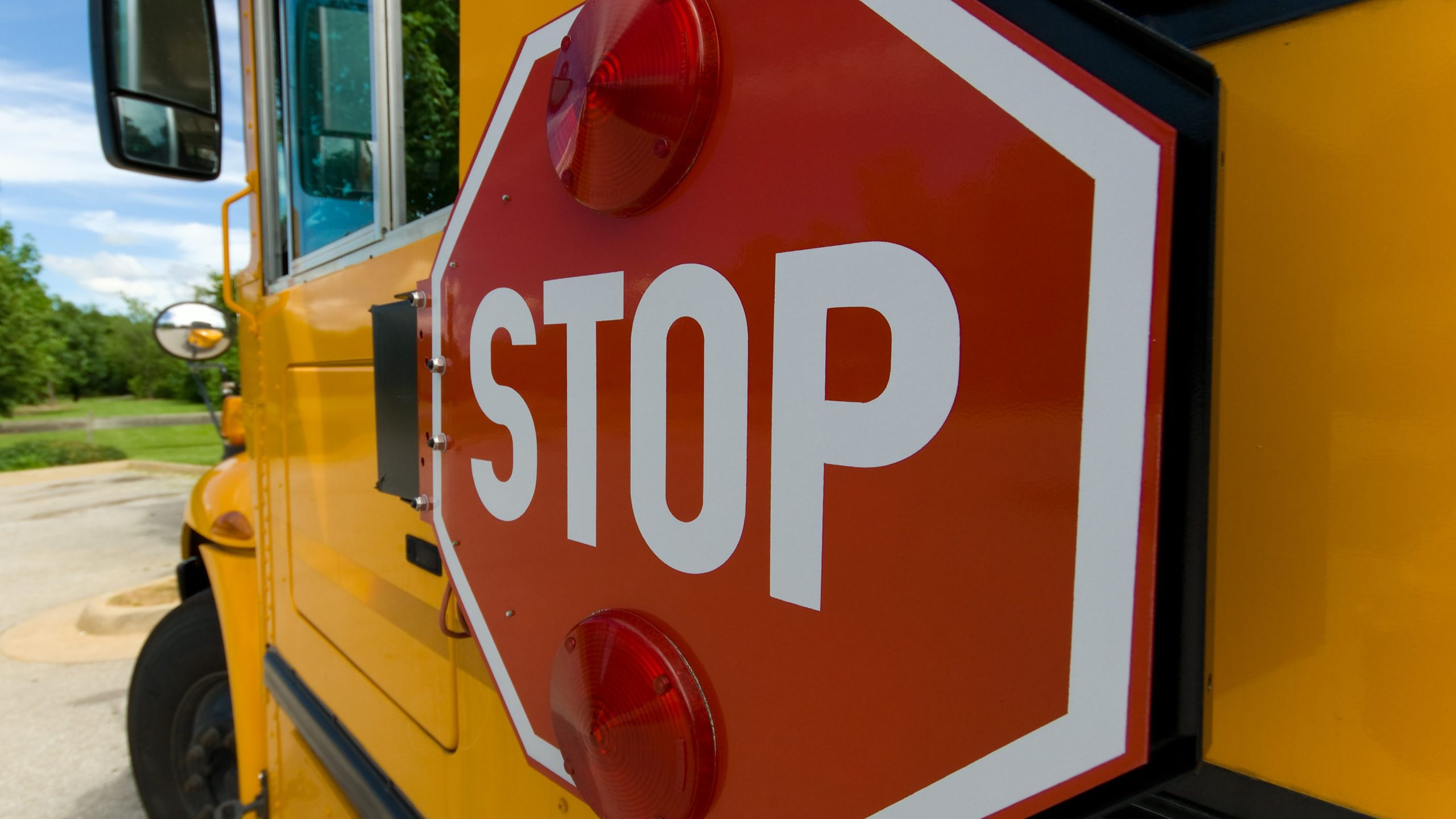 stop sign on yellow school bus making a turn against blue sky