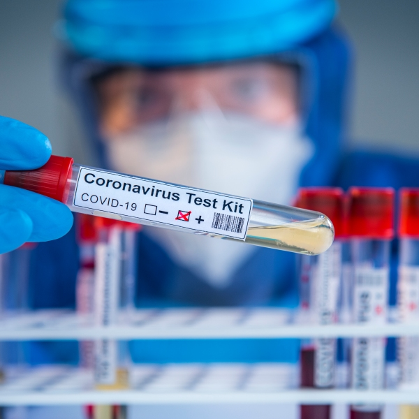 Doctor wearing highly protective suit and examining a novel coronavirus covid 19 test tubes in laboratory.