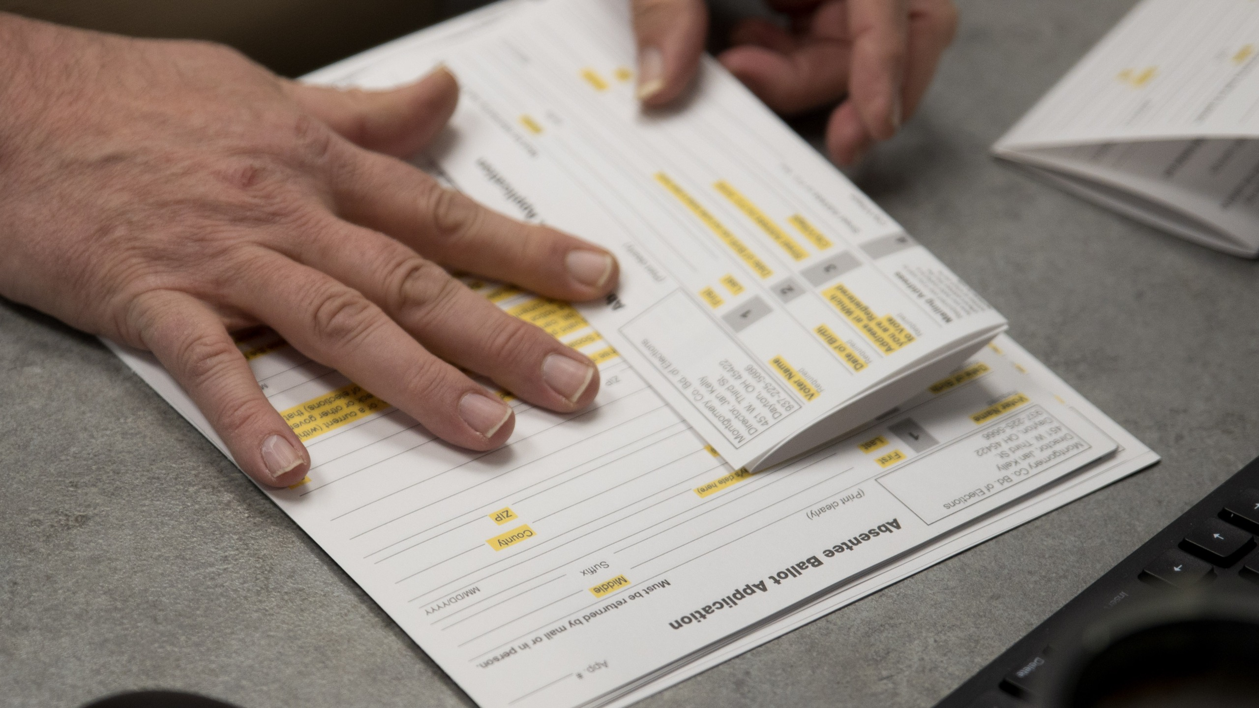 A county election worker prepares absentee ballot