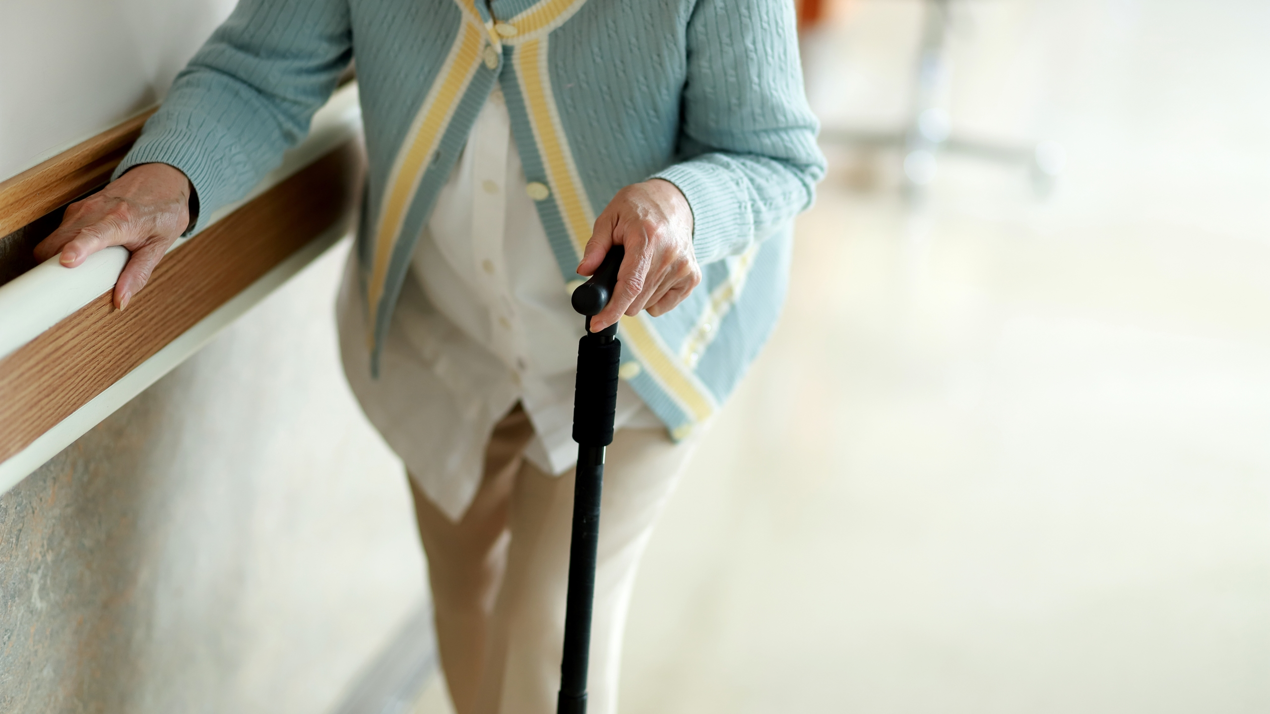 Senior woman walking with walking cane in hospital corridor