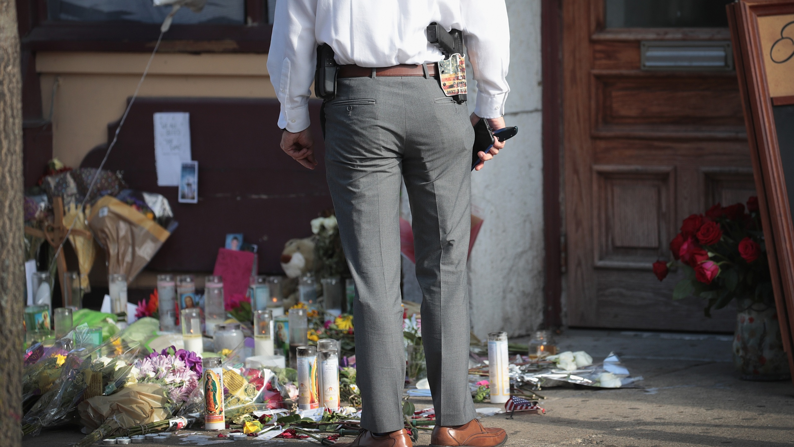 A Dayton police officer returns to search for more evidence at the scene of Sunday Morning's mass shooting in the Oregon District