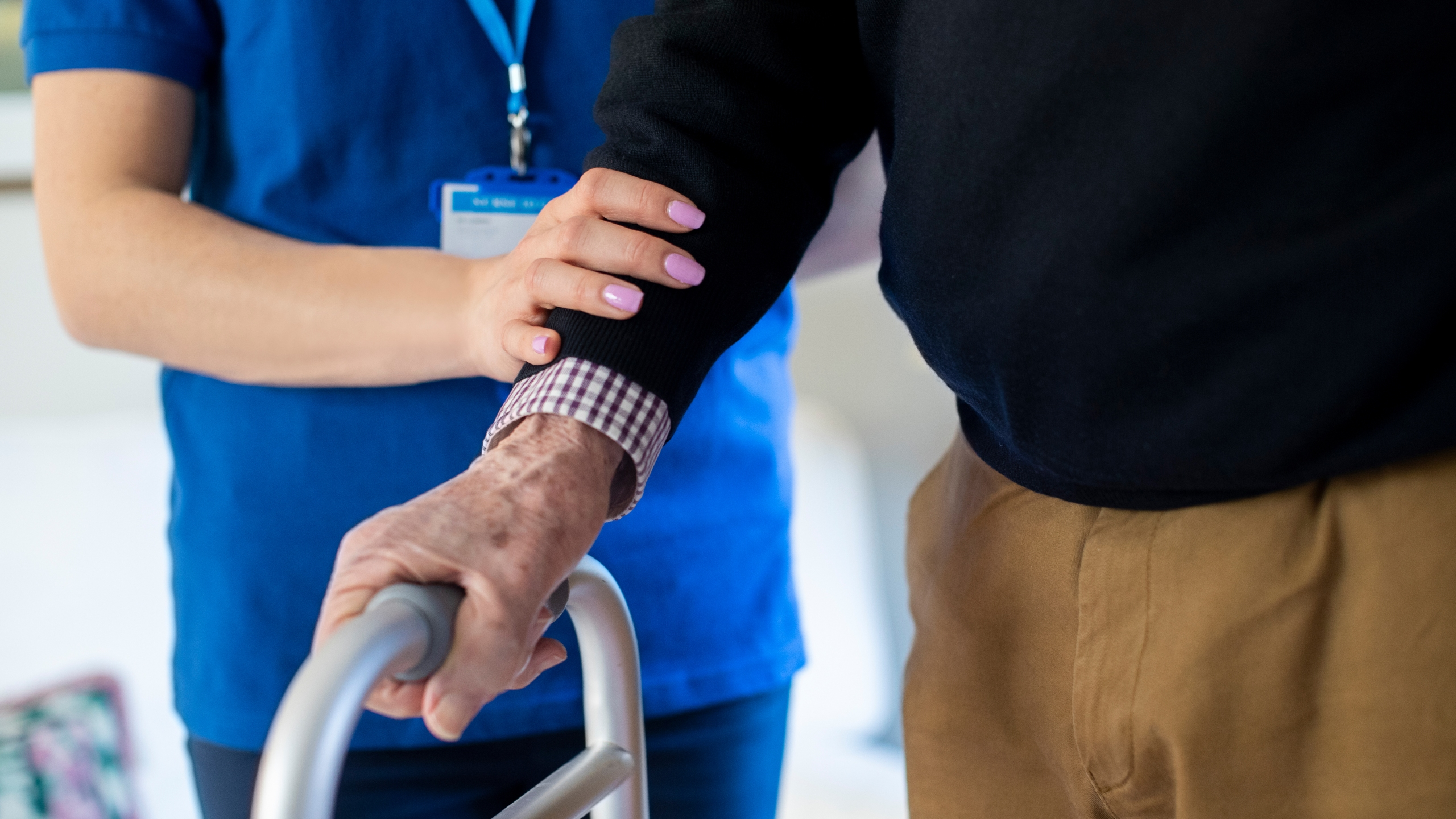Close Up Of Senior Man With Hands On Walking Frame Being Helped By Care Worker