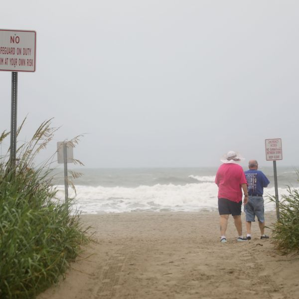 A man and woman walk onto the sand to observe the high surf as Tropical Storm Isaias approaches the South Carolina coastline in North Myrtle Beach