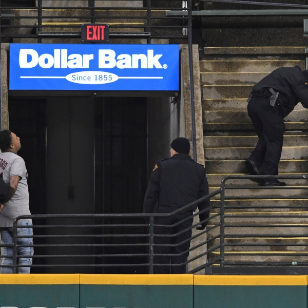 Two people who were apparently unauthorized to be in the stadium grounds are taken into custody by Cleveland police officers during the fifth inning of Game 2 of an American League wild-card baseball series between the New York Yankees and Cleveland Indians, Wednesday, Sept. 30, 2020, in Cleveland.