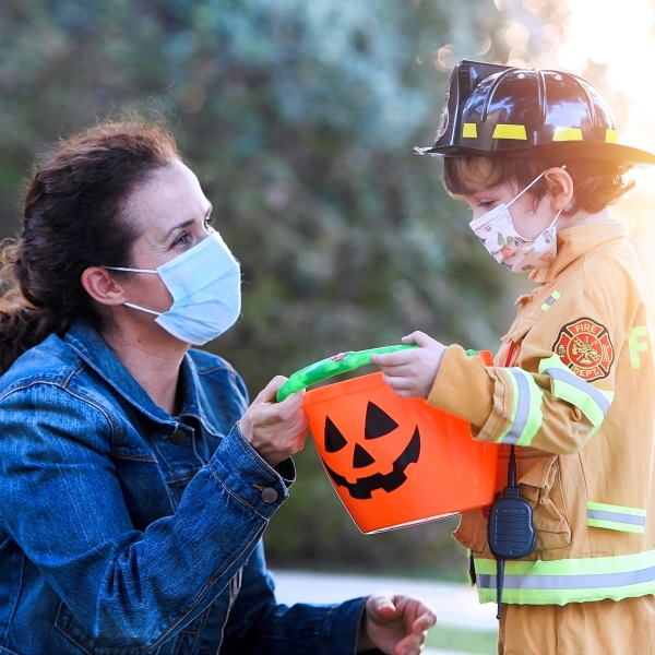 woman and a child boy wearing protective face masks before going to ask trick or treat halloween
