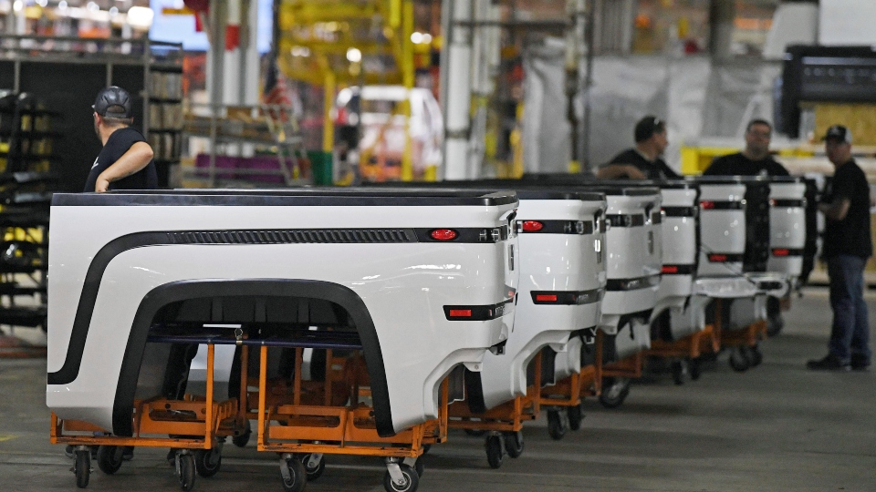 In this June 22, 2021, file photo, employees stand near Endurance truck beds during a media tour of the Lordstown Motors complex in Lordstown, Ohio.