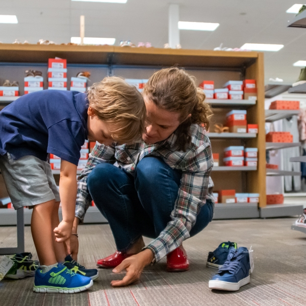 Mature woman shopping for shoes for her son