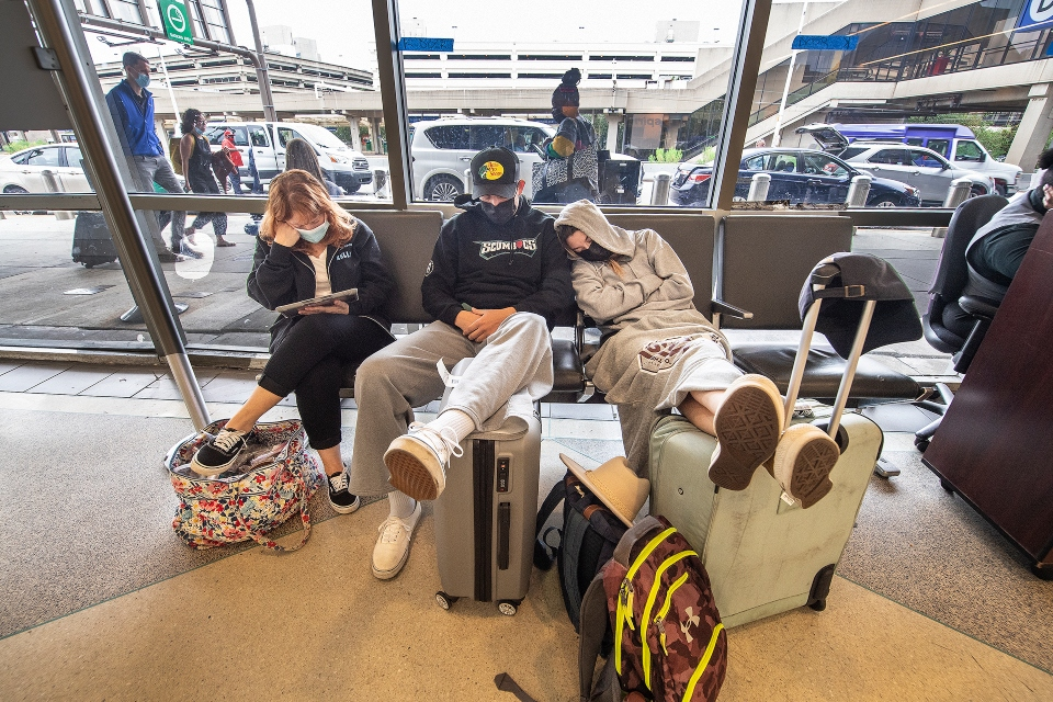Stranded travelers sleep on the seats of the ticketing waiting area, Tuesday, Aug. 3, 2021.