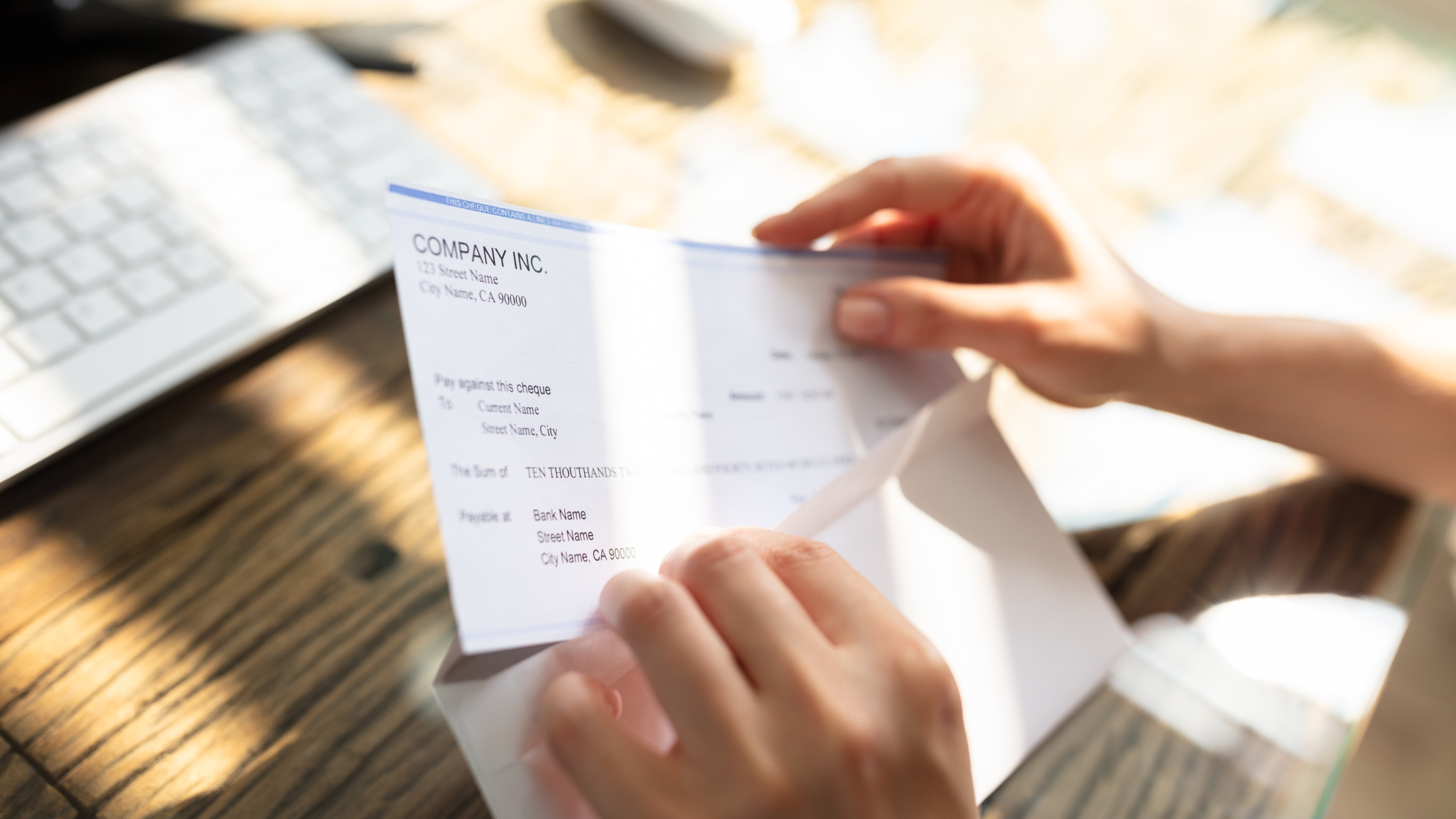 Close-up Of A Businessperson's Hand Opening Envelope With Paycheck Over Wooden Desk