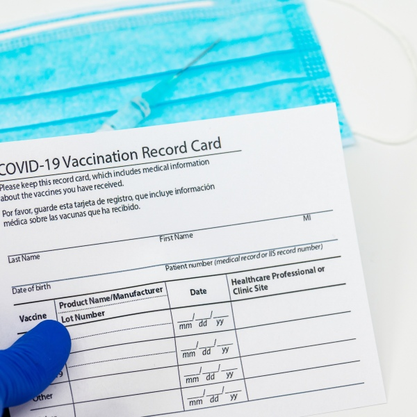 Doctor holding in hand a Covid-19 Vaccination Record card