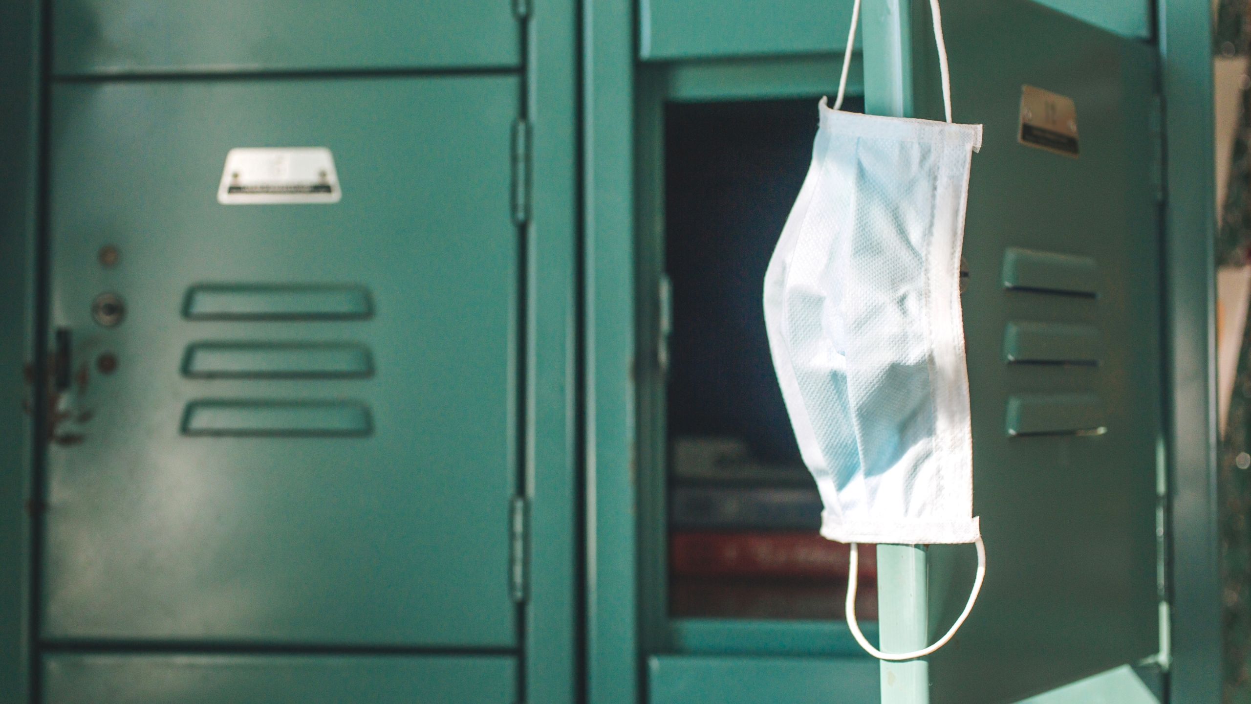 Surgical mask hanging inside school on locker. School re-openings were a controversial part of the Coronavirus pandemic, COVID-19 pandemic during 2020 and 2021.