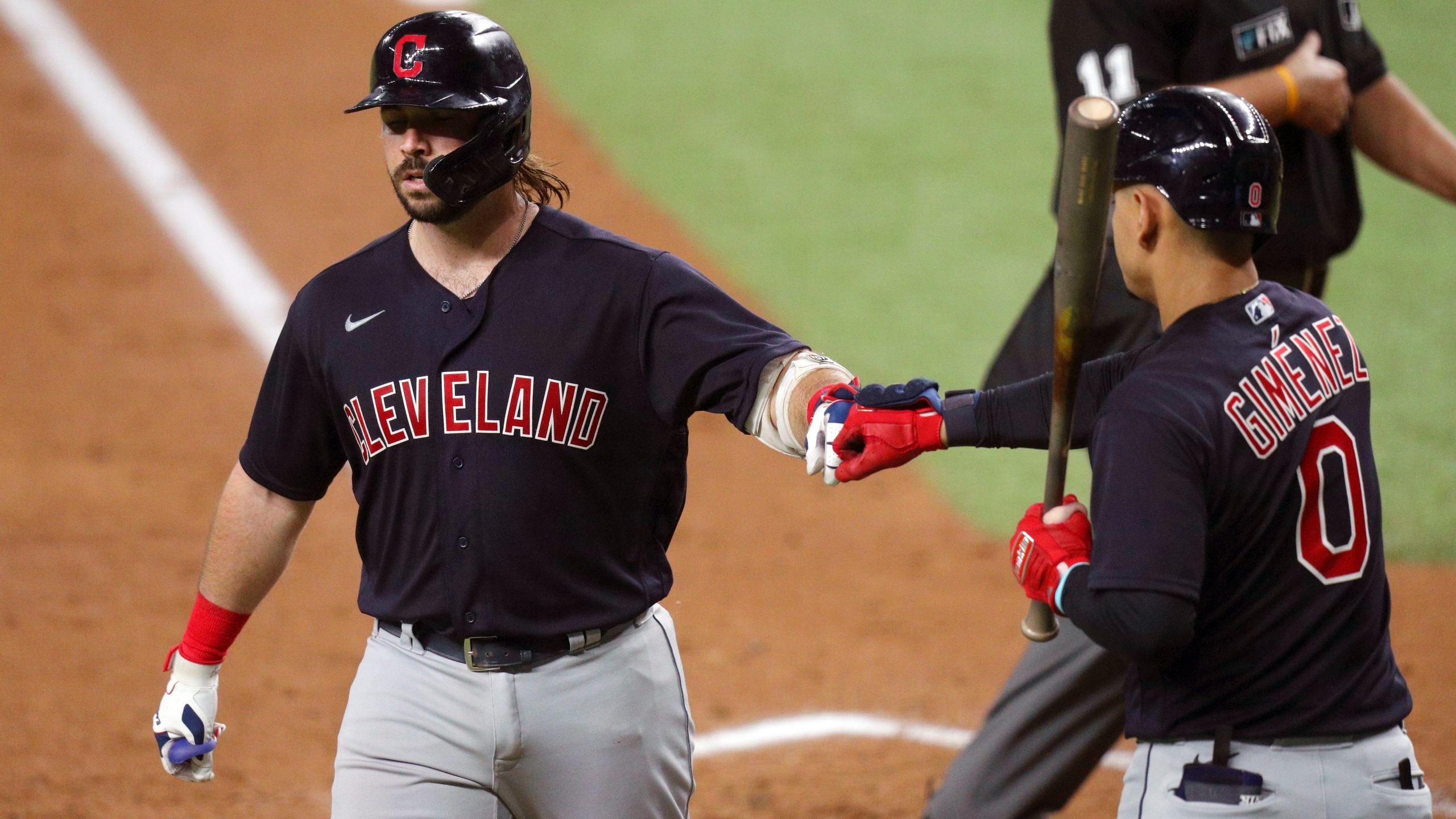 Cleveland Indians Austin Hedges (17) is greeted by Andres Gimenez (0) after scoring on a solo home run against the Texas Rangers in the third inning of a baseball game Friday, Oct. 1, 2021, in Fort Worth, Texas. (AP Photo/Richard W. Rodriguez)