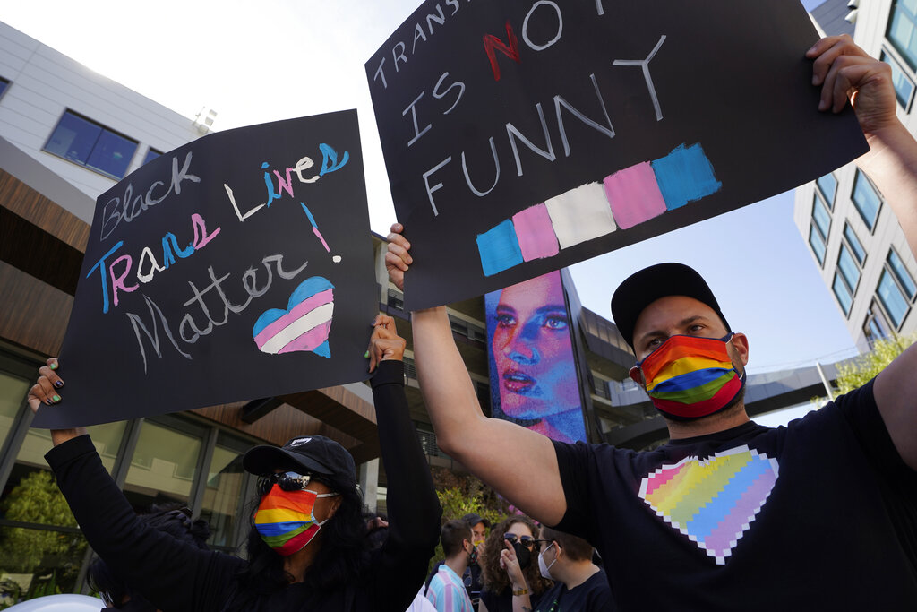 People protest outside the Netflix building on Vine Street in the Hollywood section of Los Angeles, Wednesday, Oct. 20, 2021. Critics and supporters of Dave Chappelle's Netflix special and its anti-transgender comments gathered outside the company's offices Wednesday. (AP Photo/Damian Dovarganes)