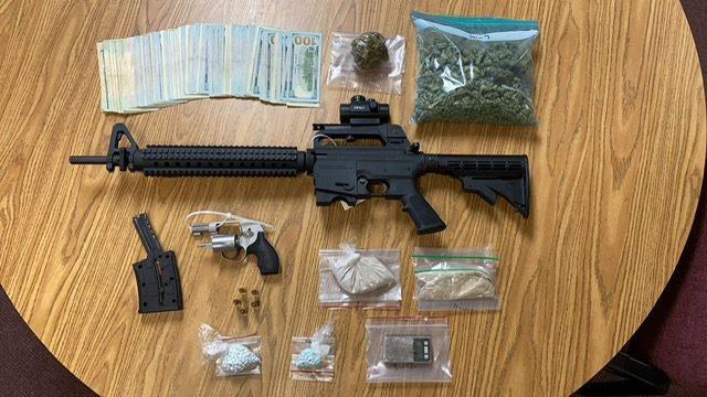 table with cash, guns and drugs in bagies