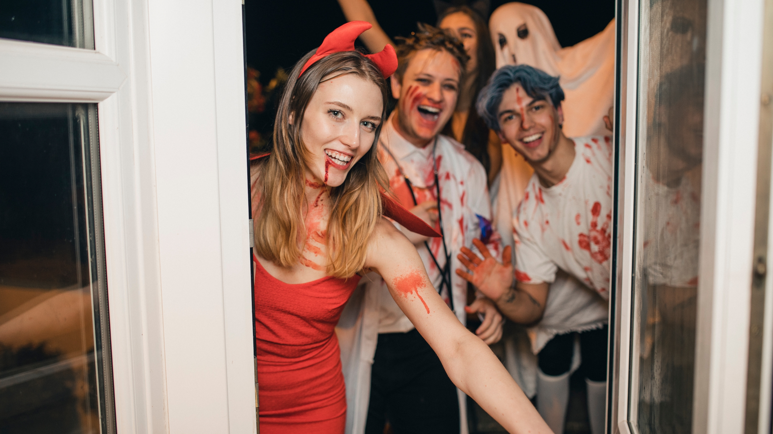 Group of friends dressed up in costumes laughing and having fun as they arrive at a Halloween party.