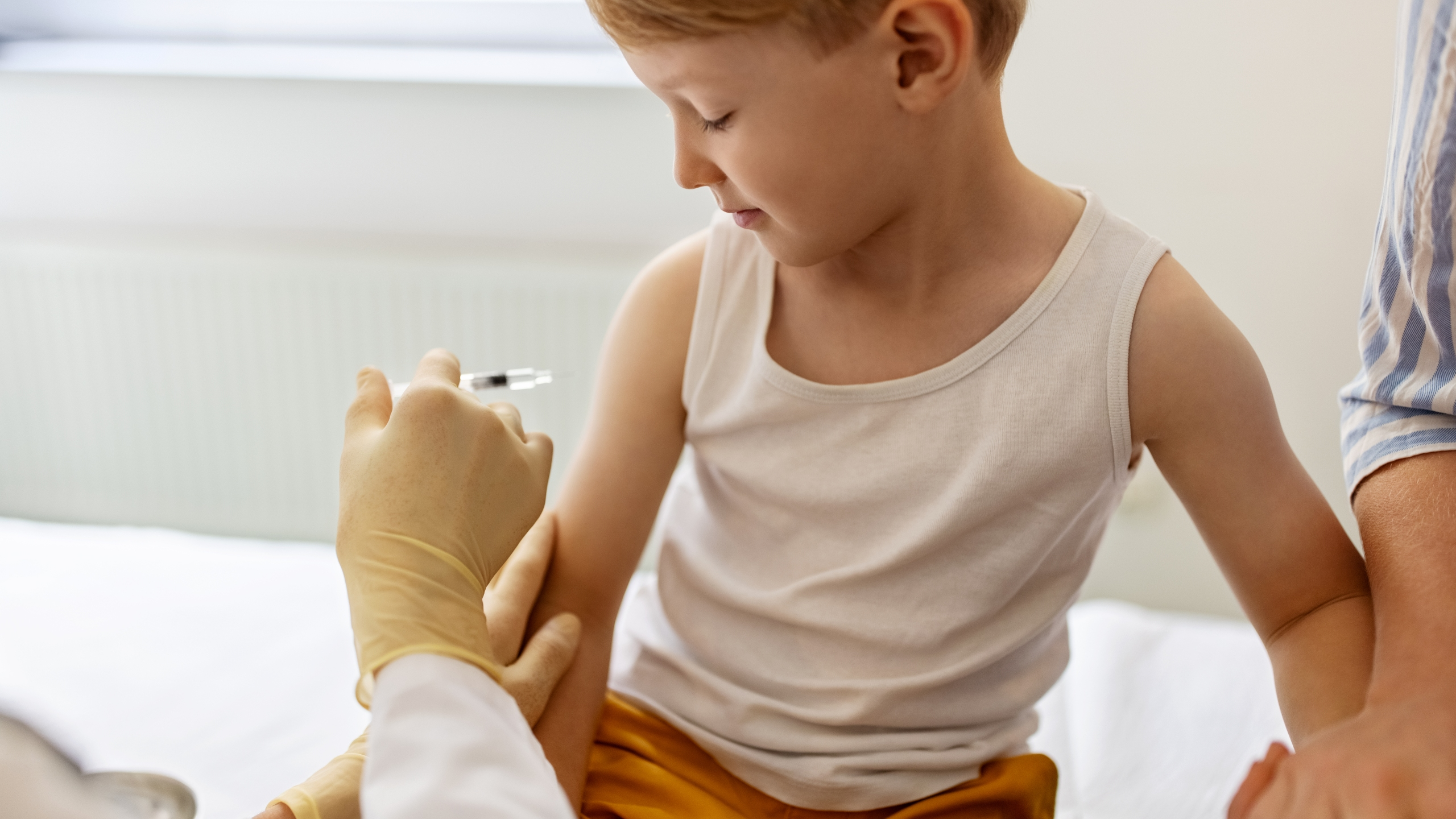 Little boy getting vaccine from a pediatrician on his arm. Boy getting flu shot at doctor's clinic.