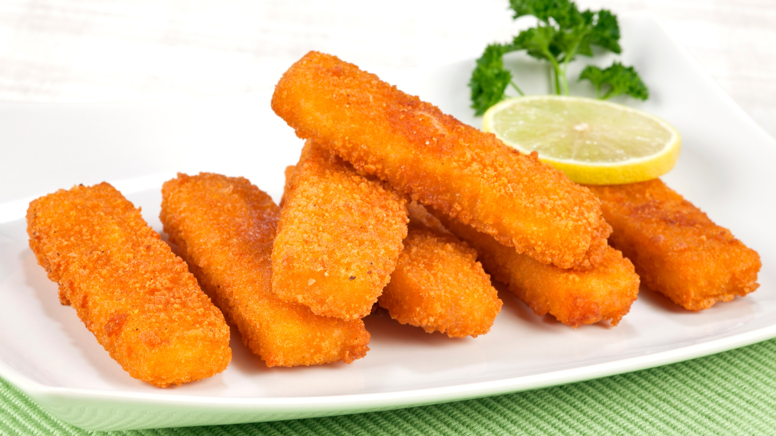 Fried fish fingers on plate. Selective focus, shallow DOF.