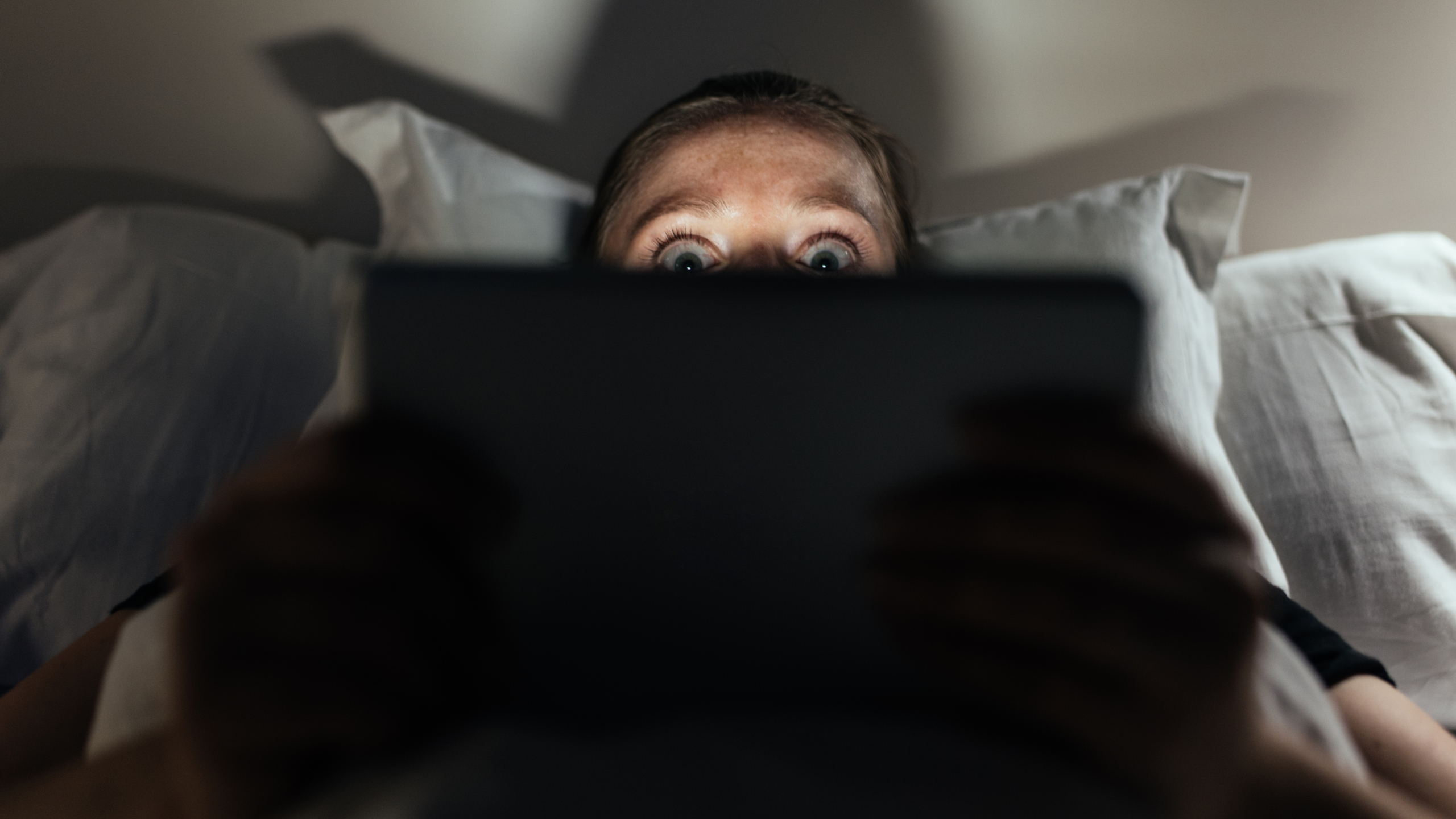 Woman using tablet pc, watching a movie late in the evening.